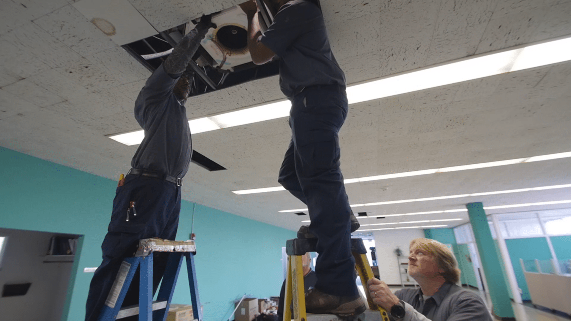 HVAC techs install HVAC system in commercial building