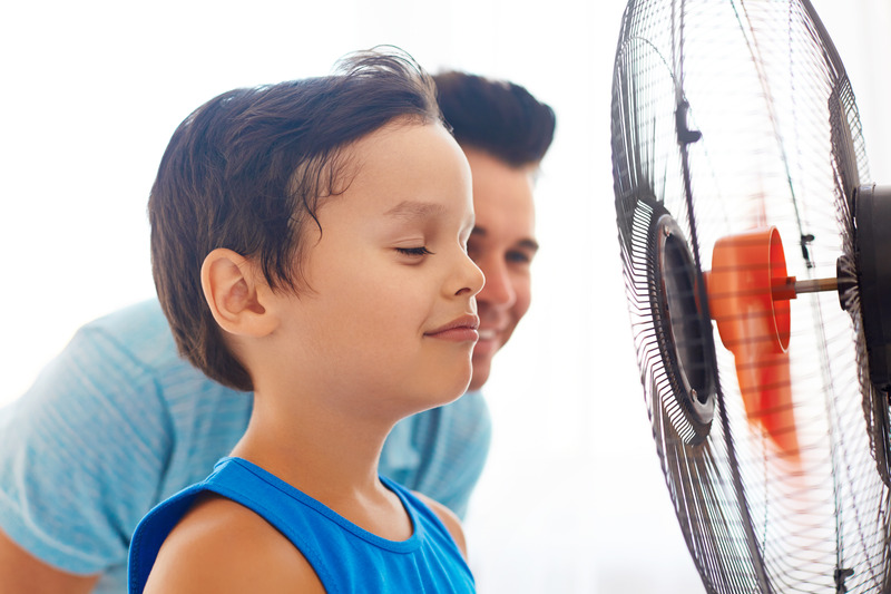 Boy with his dad cooling in front of fan.