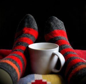 Warm socks on feet with a coffee mug between them