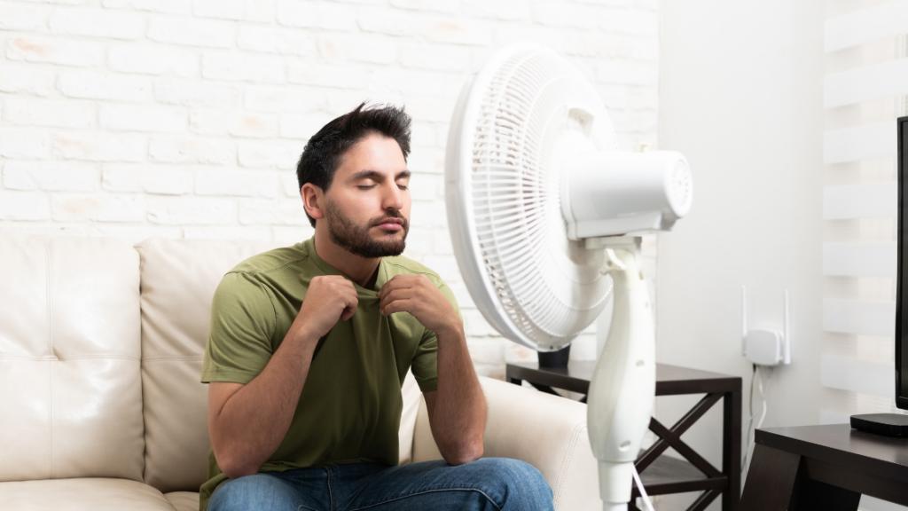 Man sitting in front of fan