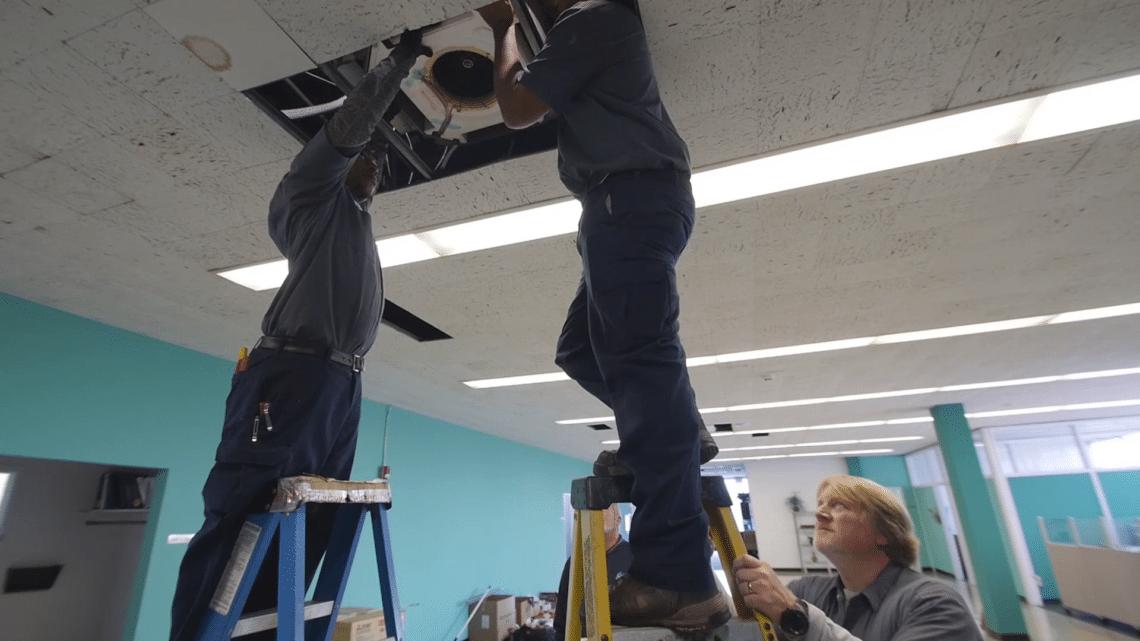 HVAC technicians installing HVAC unit